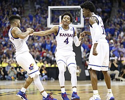 Kansas guard Frank Mason III (0) and Kansas guard Josh Jackson (11) help up Kansas guard Devonte' Graham (4) after Graham hit a three during the second half, Thursday, March 23, 2017 at Sprint Center in Kansas City, Mo.