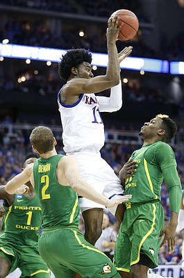 Kansas guard Josh Jackson (11) throws a pass over Oregon guard Dylan Ennis (31) to the wing during the first half on Saturday, March 25, 2017 at Sprint Center.