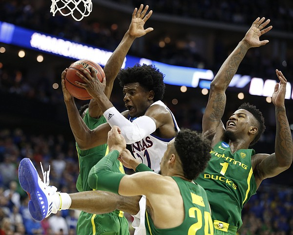 Kansas guard Josh Jackson (11) is swarmed in the paint by Oregon players including Oregon forward Dillon Brooks, front, and Oregon forward Jordan Bell (1) during the second half on Saturday, March 25, 2017 at Sprint Center.