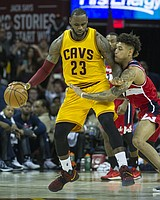Cleveland Cavaliers' LeBron James (23) keeps the ball from Washington Wizards' Kelly Oubre Jr. (12) during the second half of an NBA basketball game in Cleveland, Saturday, March 25, 2017. (AP Photo/Phil Long)