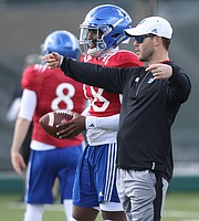 New Kansas quarterbacks coach Garrett Riley gives some direction to quarterback Tyriek Starks during practice on Thursday, April 6, 2017.