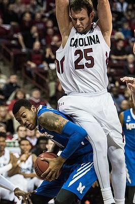 South Carolina forward Mindaugas Kacinas (25) fouls Memphis forward K.J. Lawson, left, during the first half of an NCAA college basketball game Saturday, Jan. 2, 2016, in Columbia, S.C. (AP Photo/Sean Rayford)