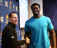 Kansas offensive tackle Hakeem Adeniji is congratulated by head coach David Beaty after being selected third overall during a spring game player draft on Wednesday, April 12, 2017 at the Anderson Family Football Complex.