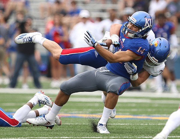 Team KU receiver Kerr Johnson Jr. (14) is taken to the turf by Team Jayhawk linebacker Joe Dineen Jr. (29) during the first quarter of the 2017 Spring Game on Saturday, April 15 at Memorial Stadium.
