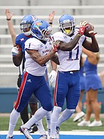 Team Jayhawk wide receiver Steven Sims Jr. (11) gets a shove from Team Jayhawk wide receiver LaQuvionte Gonzalez (1) after Sims' touchdown during the second quarter of the 2017 Spring Game on Saturday, April 15 at Memorial Stadium.