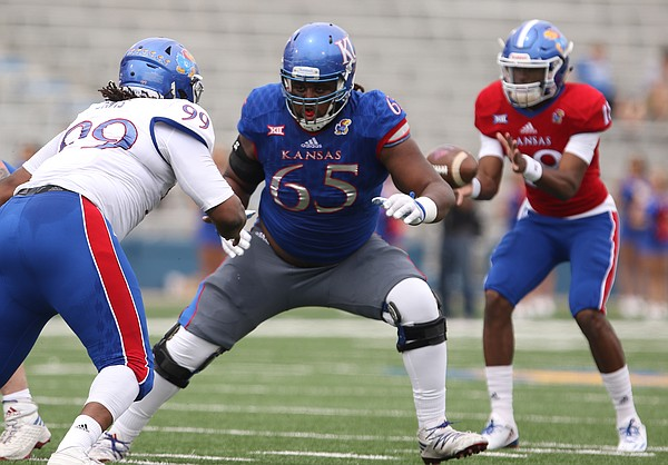Team KU offensive lineman Jayson Rhodes (65) looks to fend off Team Jayhawk defensive tackle DeeIsaac Davis (99) during the third quarter of the 2017 Spring Game on Saturday, April 15 at Memorial Stadium.