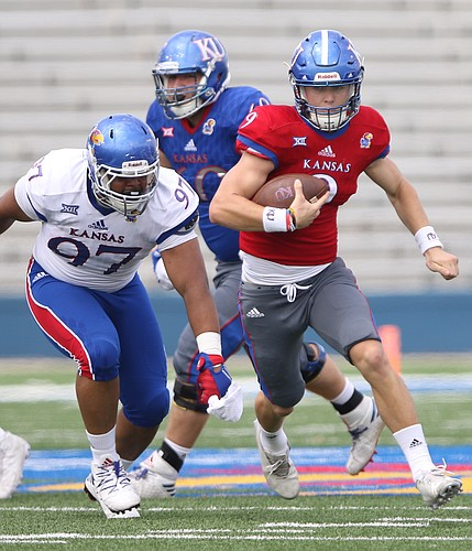 Team KU quarterback Carter Stanley (9) escapes Team Jayhawk defensive end Kellen Ash (97) during the third quarter of the 2017 Spring Game on Saturday, April 15 at Memorial Stadium.