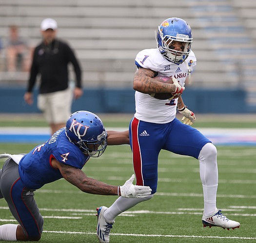 Team Jayhawk wide receiver LaQuvionte Gonzalez (1) escapes a tackle from Team KU safety Shaquille Richmond (4) during the first quarter of the 2017 Spring Game on Saturday, April 15 at Memorial Stadium.