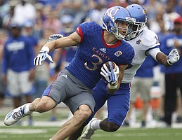 Kansas wide receiver Chase Harrell (3) is tackled by cornerback Kyle Mayberry (16) after a catch during the spring game on Saturday, April 15, at Memorial Stadium.
