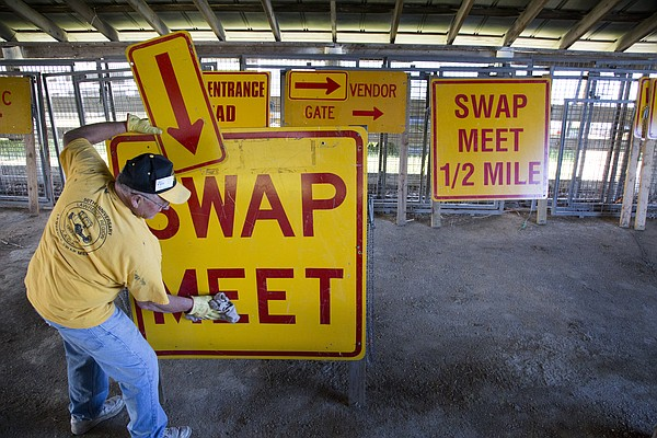 In this file photo from May 5, 2016, Joe Arneson, of Lawrence, wipes down a sign in preparation for the annual Lawrence Region Antique Auto Club of America Swap Meet at the Douglas County Fairgrounds.