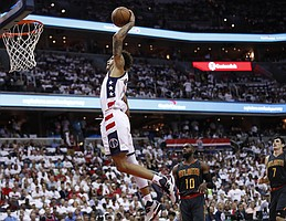 Washington Wizards forward Kelly Oubre Jr. (12) jumps to dunk the ball while Atlanta Hawks guard Tim Hardaway Jr. (10) and teammate Ersan Ilyasova (7) watch during the first half in Game 1 of a first-round NBA basketball playoff series, in Washington, Sunday, April 16, 2017. The Wizards won 114-107. (AP Photo/Manuel Balce Ceneta)