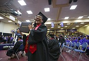 Haskell graduate Angela Nasewytewa, of the Hopi, Pascua Yaqui and Pima tribes, smiles with her diploma as family members take her photo during the Haskell Indian Nations University Commencement at Coffin Sports Complex on Friday, May 19, 2017.