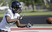 Lawrence High School senior Ekow Boye-Doe (12) participates in pass catching drills during a summer football practice Wednesday at LHS.