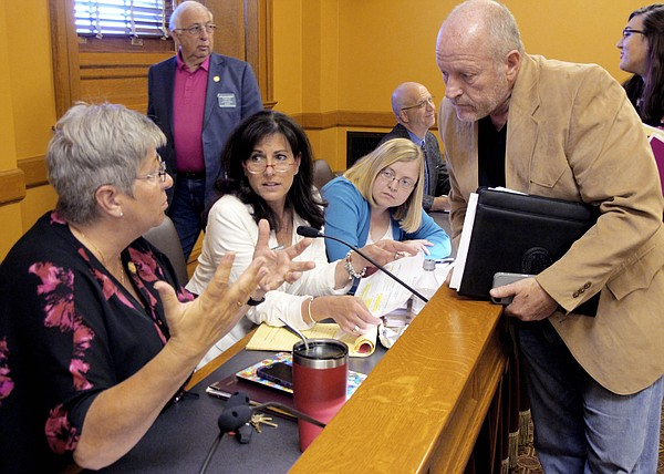 State Rep. Brenda Landwehr, left, R-Wichita, confers with lead House negotiator Larry Campbell, right, R-Olathe, during a break in talks with the Senate on school funding legislation, Friday, June 2, 2017, at the Statehouse in Topeka, Kan. Watching them are Rep. Melissa Rooker, center left, R-Fairway, and Melinda Gaul, center right, an aide to House Speaker Ron Ryckman Jr., R-Olathe. (AP Photo/John Hanna)