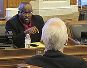 Kansas state Rep. K.C. Ohaebosim, left, D-Wichita, makes a point in a conversation with Rep. Boog Highberger, right, D-Lawrence, before a House vote on overriding Republican Gov. Sam Brownback's veto of a tax increase to fix the state budget, Tuesday, June 6, 2017, in Topeka, Kan. Legislators have overridden the veto, and Ohaebosim and Highberger supported the effort. (AP Photo/John Hanna)