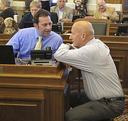 Kansas state Reps. Troy Waymaster, left, R-Bunker Hill, and Russ Jennings, R-Lakin, confer before the House's debate on overriding Republican Gov. Sam Brownback's veto of a bill increasing income taxes to fix the state budget, Tuesday, June 6, 2017, in Topeka, Kan. Both Jennings and Waymaster, the House Appropriations Committee chairman, voted to override. (AP Photo/John Hanna)