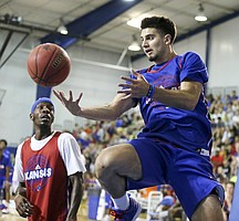 Blue Team guard Sam Cunliffe dishes a pass beyond defender Tyshawn Taylor during a scrimmage on Wednesday, June 7, 2017 at the Horejsi Family Athletics Center.