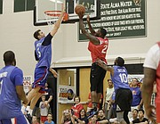 Jeff Withey, left, jumps to block a shot by Mario Little during the 2017 Rock Chalk Roundball Classic Thursday evening at Lawrence Free State High School. The annual charity event benefits local families fighting cancer