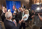 Kansas Secretary of State Kris Kobach carries his two-year-old daughter Josie as he greets supporters after announcing his campaign for governor on Thursday, June 8, 2017 at the Thompson Barn in Lenexa, Kan.