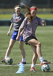 Free State's Kate Odgers weaves though a set of cones during soccer camp on Monday, June 12, 2017. In back is Sabrea Platz, a FSHS graduate who was assisting with the camp.