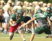 Free State running back Gage Foster looks to shake a Shawnee Mission South defender during the Baker Contact Camp on Tuesday, June 13, 2017 at Lawrence High School.