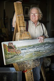 Lawrence resident Peter Johnson is pictured with one of his paintings of the Kansas River on Thursday, June 22, 2017, at his studio in North Lawrence. Johnson, who is a painter, printmaker, and who also enjoys drawing, will be showing his work at the Summer Fest arts fair on June 25 at South Park.