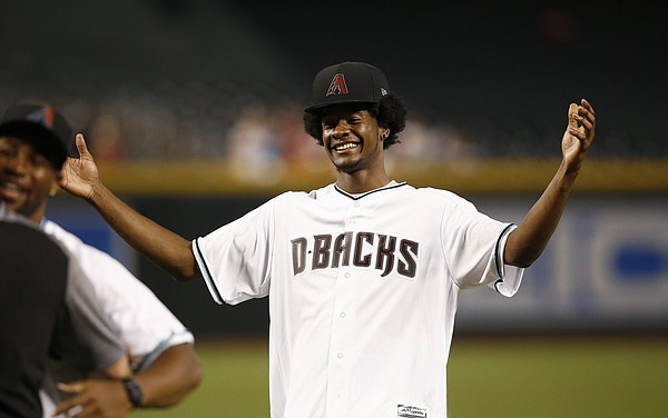 Former KU star Josh Jackson laughs and throws up his hands after firing out a horrific ceremonial first pitch at Friday's Arizona Diamondbacks game. (AP Photo)