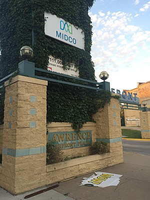 A Midco sign is in place outside Riverfront Plaza, Tuesday evening, June 27, 2017, after workers removed WOW signs, at bottom, from the company's properties.