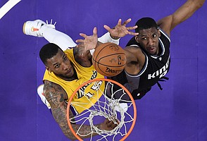 Los Angeles Lakers forward Thomas Robinson, left, and Sacramento Kings guard Langston Galloway reach for a rebound during the second half of an NBA basketball game, Friday, April 7, 2017, in Los Angeles. The Lakers won 98-94. (AP Photo/Mark J. Terrill)