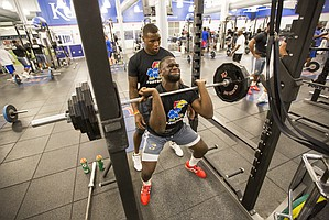 Kansas defensive end Dorance Armstrong spots fellow position player Josh Ehambe during a set of squats at the Anderson Family Football Complex on Thursday, June 29, 2017.
