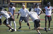 Lawrence High head football coach Dirk Wedd follows the motion of the running backs as he oversees his camp on Monday, July 10, 2017 at LHS.