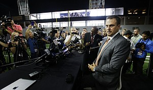 Texas head football coach Tom Herman takes a seat before speaking to reporters during the Big 12 NCAA college football media day in Frisco, Texas, Tuesday, July 18, 2017.