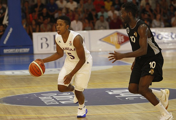 Kansas guard Charlie Moore, left, is chased by HSC Roma's Aristide Mouaha during their basketball game in Rome, Wednesday, Aug. 2, 2017. (AP Photo/Riccardo De Luca)