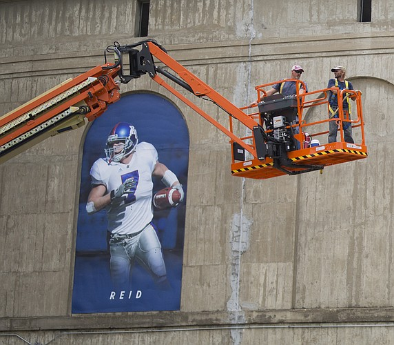 Workers in a cherry picker come down next to a banner of former Kansas linebacker Nick Reid, while doing some exterior work on Memorial Stadium, Monday, Aug. 7, 2017.