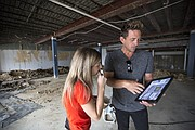 Allison McEldowney, a marketing creative director, and Zach Lee, a designer hired by the owners of McLain's Market in Overland Park, look through a tablet with design plans within the former Jayhawk Bookstore location, 1420 Crescent Road on Monday, Aug. 14, 2017.