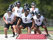 Lawrence High players weave through a set of pads on Monday, Aug. 14, 2017 at the high school. Monday was the first day for football practice.