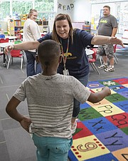 Pinckney Elementary School first-grader Cheyton Walter runs to hug his former kindergarten teacher Carly Glennon in her new kindergarten classroom during an open house. The school was renovated during the last year and added a new art room, two new kindergarten rooms with restrooms attached, two new fifth-grade rooms, multiple learning pockets, a new cafeteria and kitchen.