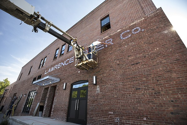 Workers with Star Signs Inc. work on the exterior signage at the Lawrence Beer Company on Thursday, Aug. 24, 2017.