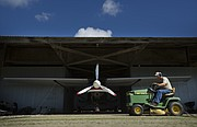 Vinland Valley Aerodrome groundskeeper Ken Kern drives his mower past a plane on Tuesday, Aug. 29, 2017 at the Vinland Airport.
