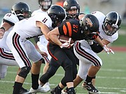 Lawrence High defenders Caleb Mondi (11) and Isaac Flint, right, bring down Shawnee Mission Northwest running back Jamie Alexander during the first quarter on Thursday, Aug. 31, 2017 at Shawnee Mission North District Stadium.
