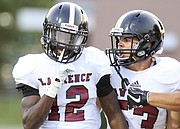 Lawrence High receiver Ekow Boye-Doe silences the Shawnee Mission Northwest crowd after a touchdown as he celebrates with teammate Jacob Mills during the first quarter on Thursday, Aug. 31, 2017 at Shawnee Mission North District Stadium.
