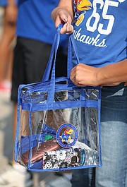 A Kansas fan zips up her clear plastic bag after moving through metal detectors prior to kickoff against Southeast Missouri on Saturday, Sept. 2, 2017 at Memorial Stadium.