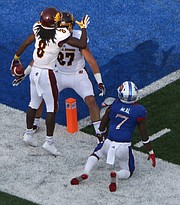 Kansas defensive back Derrick Neal (7) watches Central Michigan players Cory Wiilis (8) and Logan Hessbrook celebrate Willis's touchdown in the first half of the Jayhawks game against Central Michigan Saturday, Sept. 9 at Memorial Stadium.