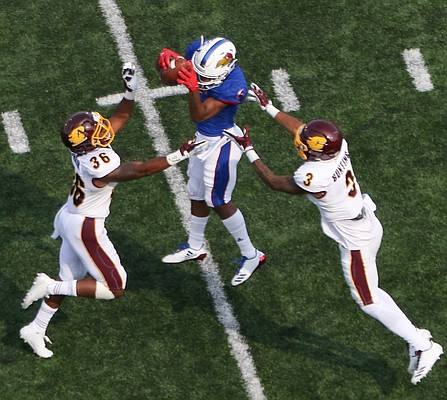 Kansas wide receiver Quan Hampton (6) jumps in the air to catch a pass between defender during the Jayhawks game against Central Michigan Saturday, Sept. 9 at Memorial Stadium. When Hampton landed CMU defenders stripped him of the ball and were awarded an interception call.