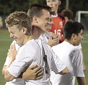 Free State sophomore Pete Junge (7) gets hugged by his teammates after scoring the game-winning goal in the Firebirds' 5-4 overtime victory over De Soto on Monday at FSHS.