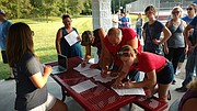 Area residents gather and sign petitions Saturday at Chieftain Park in Tonganoxie during an informational meeting for Citizens Against Project Sunset, a group that opposes the proposed Tyson chicken facility.