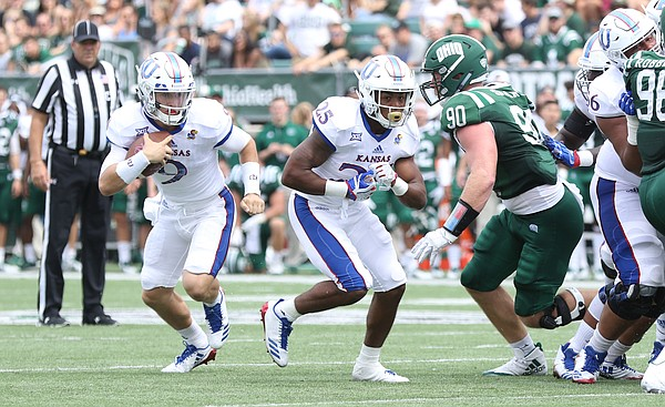Kansas quarterback Carter Stanley (9) look to cut around the Ohio defense during the second quarter on Saturday, Sept. 16, 2017 at Peden Stadium in Athens, Ohio.