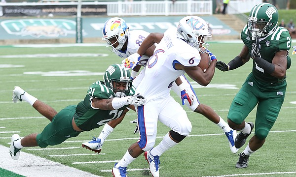 Kansas wide receiver Quan Hampton (6) is pushed out of bounds by Ohio cornerback Jalen Fox (21) and Ohio cornerback Mayne Williams (2) during the fourth quarter on Saturday, Sept. 16, 2017 at Peden Stadium in Athens, Ohio.