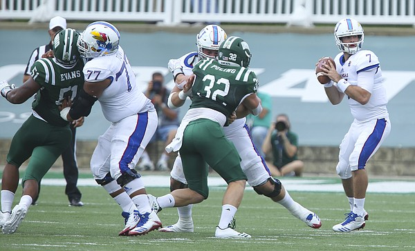 Kansas offensive lineman Andru Tovi (77) and Kansas offensive lineman Mesa Ribordy work to push aside Ohio defensive lineman Will Evans (51) and Ohio linebacker Quentin Poling (32) as Kansas quarterback Peyton Bender (7) looks to throw during the first quarter on Saturday, Sept. 16, 2017 at Peden Stadium in Athens, Ohio.