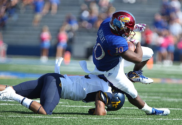 Kansas sophomore running back Khalil Herbert is taken off of his feet by a West Virginia defender during the first quarter on Saturday, Sept. 23, 2017 at Memorial Stadium.